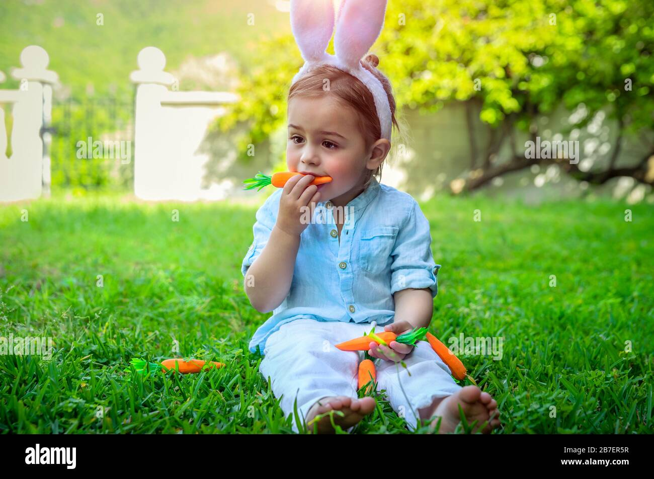 Cute little boy dressed as a bunny, baby eating carrots, happy ...