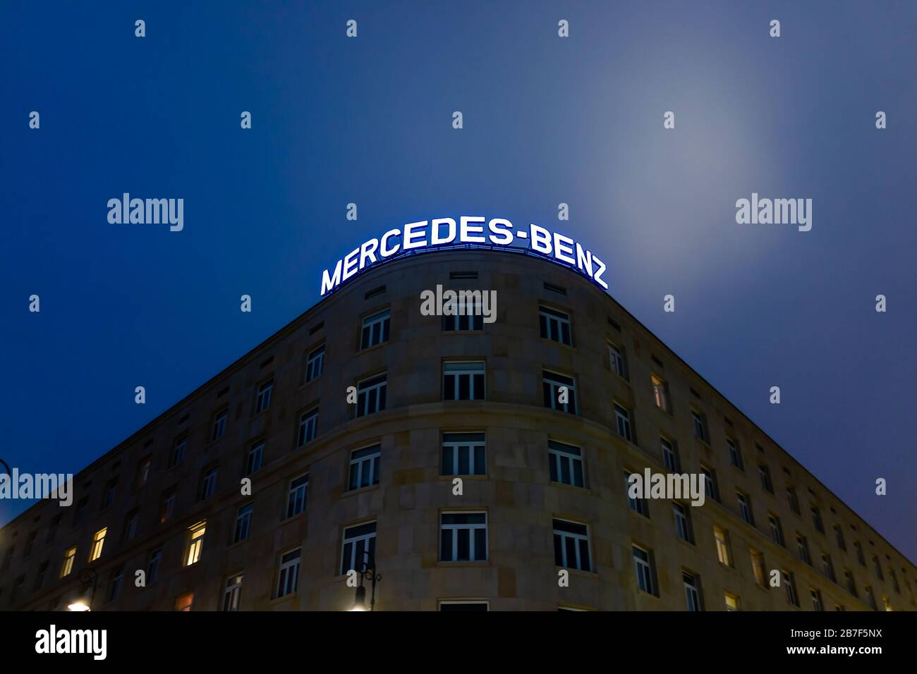 Warsaw, Poland - December 22, 2019: Dom Bez Kantow (House without Edges) housing boutique hotel at night with Mercedez-Benz neon light sign in old tow Stock Photo