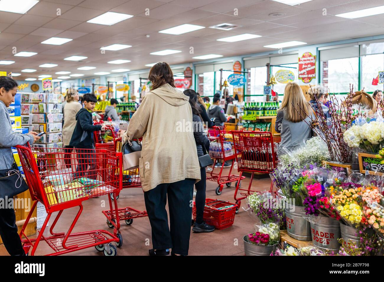 Reston, USA - March 13, 2020: Long lines in Trader Joe's store, people by shopping cart buying grocery products, paying at cashier registers in prepar Stock Photo