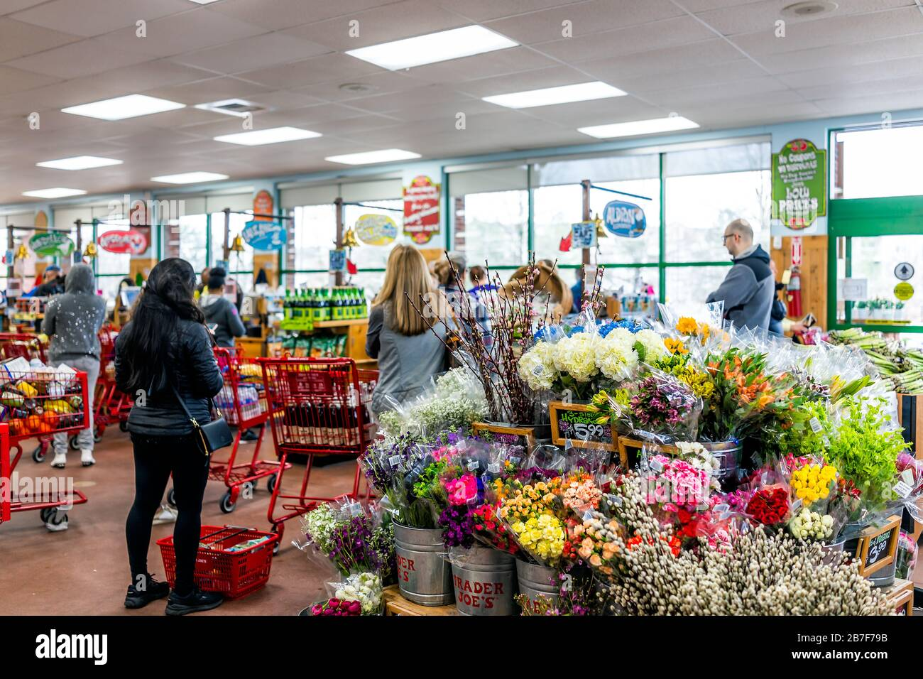 Reston, USA - March 13, 2020: Long lines in Trader Joe's store with people by shopping cart buying grocery products, paying at cashier registers in pr Stock Photo