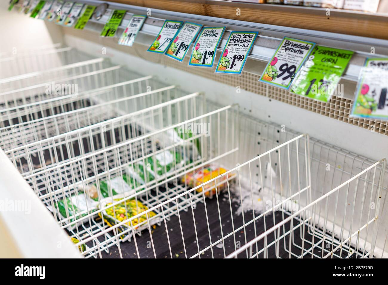 Reston, USA - March 13, 2020: Sold out empty refrigerator freezer shelf racks with frozen vegetable grocery food produce, price tags at Trader Joe's s Stock Photo