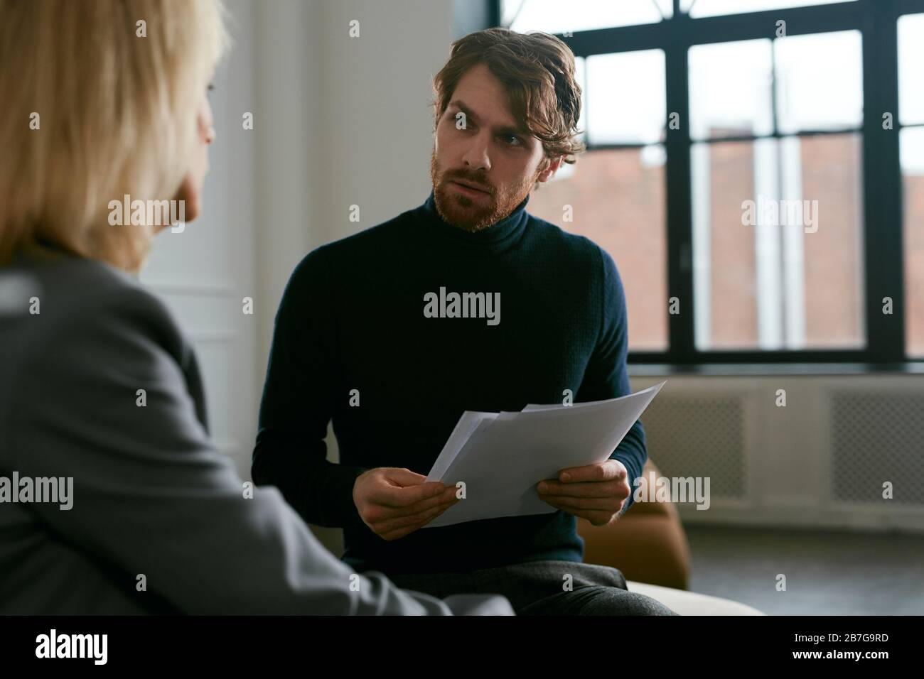 Waist up portrait of handsome bearded man talking to female partner while discussing work in office interior, copy space Stock Photo