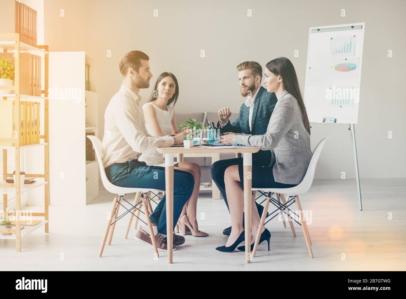Young business people in formalwear discussing something seriously while sitting together at the table in light modern workplace Stock Photo