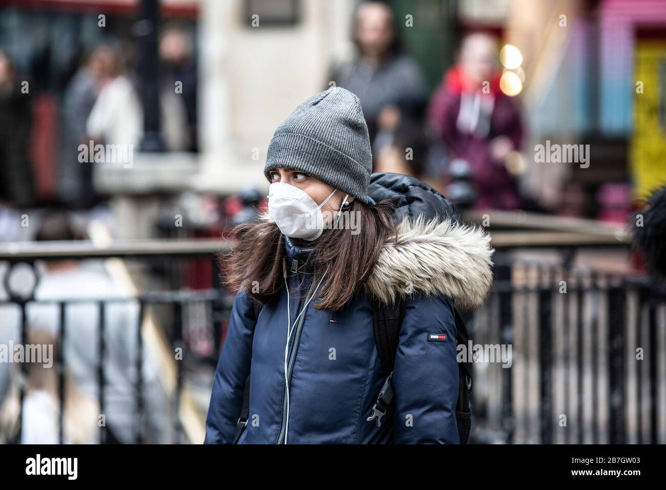 Travellers take precautions by wearing face masks in the West End of London against infection of the Coronavirus Covid19 pandemic, England, UK Stock Photo