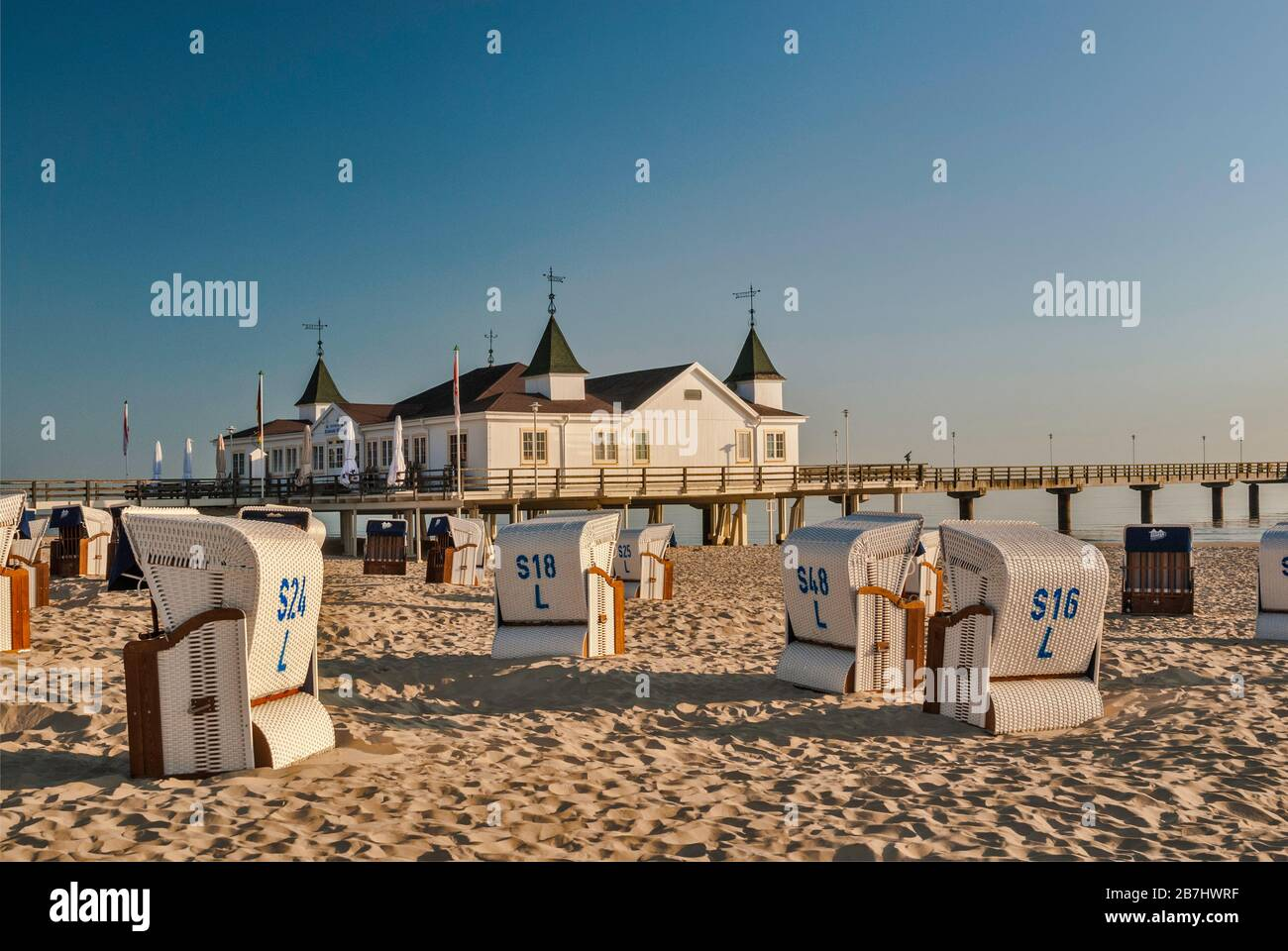 Wicker beach chairs and Seebrücke pier in Ahlbeck at Usedom Island in Mecklenburg-West Pomerania, Germany Stock Photo