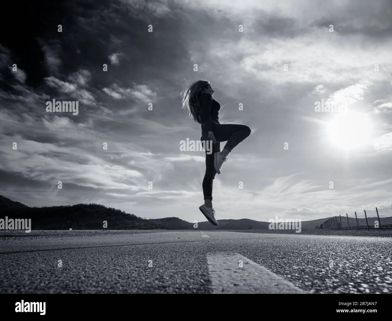 Slight jump on road low view teen girl wearing Red pullover denim pants denims sneakers silhouette scenic scenery landscape Stock Photo