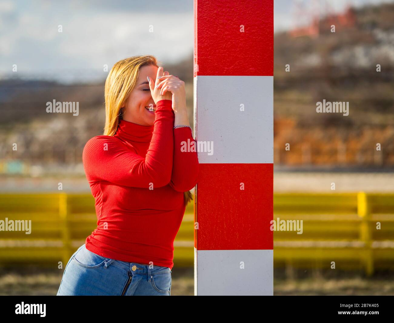 Hiding face very shy teen girl dont see me standing inclined Red-White stripped column golden hair Stock Photo