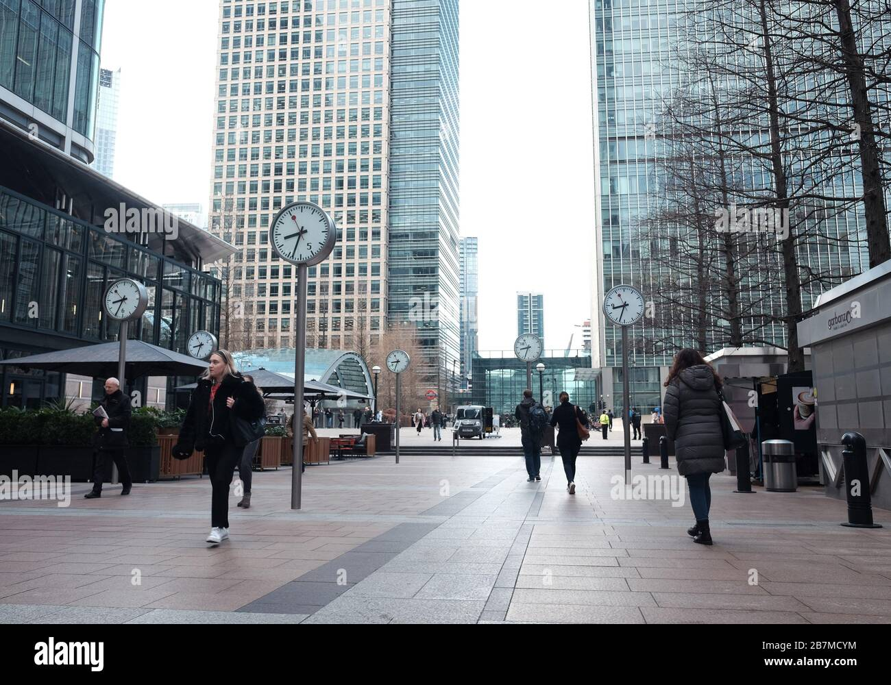 People walk across Reuters Plaza in Canary Wharf, London, the day after Prime Minister Boris Johnson called on people to stay away from pubs, clubs and theatres, work from home if possible and avoid all non-essential contacts and travel in order to reduce the impact of the coronavirus pandemic. Stock Photo