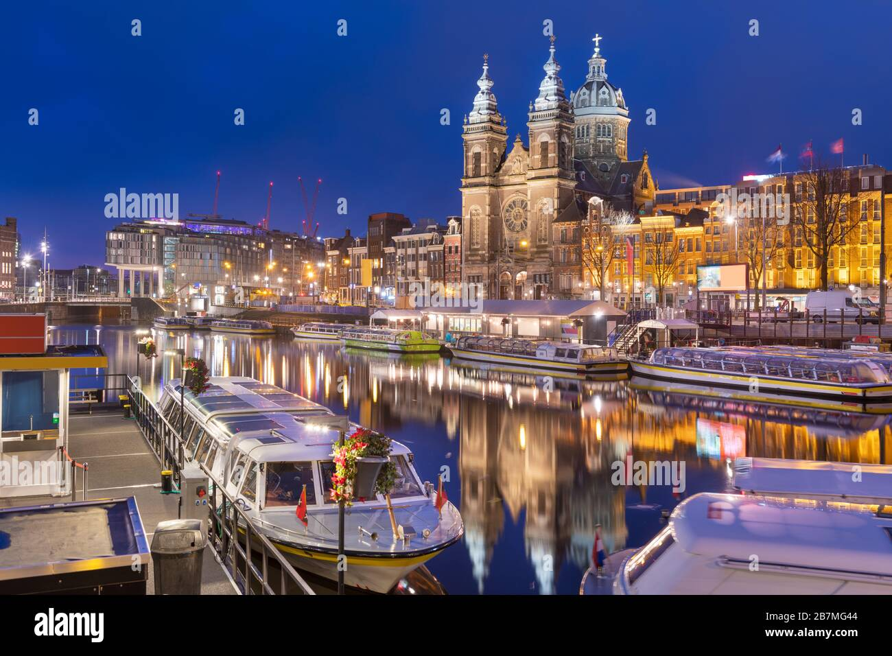 Amsterdam, Netherlands canal scene at night with Basilica of Saint Nicholas and riverboats. Stock Photo