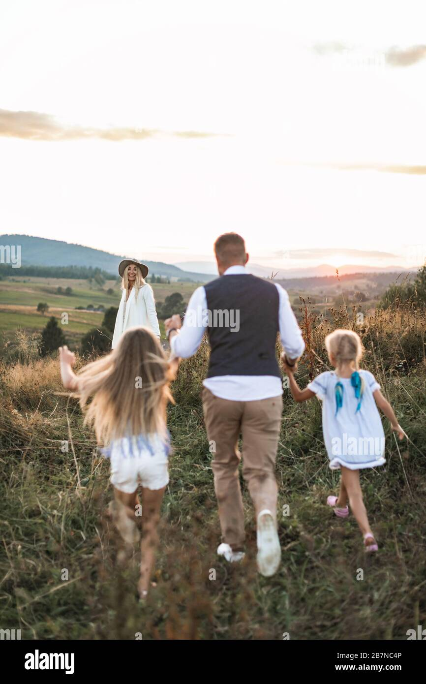 Stylilsh family, father, mother and two little cute daughters having fun and running in summer wild field. Stock Photo