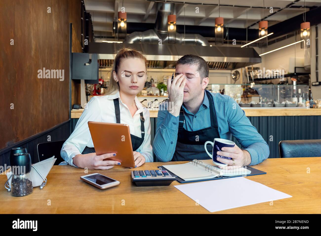 Worried business owners calculating finances - Small restaurant entrepreneurs SME go bankrupt due to Coronavirus pandemic - Young woman and man with h Stock Photo