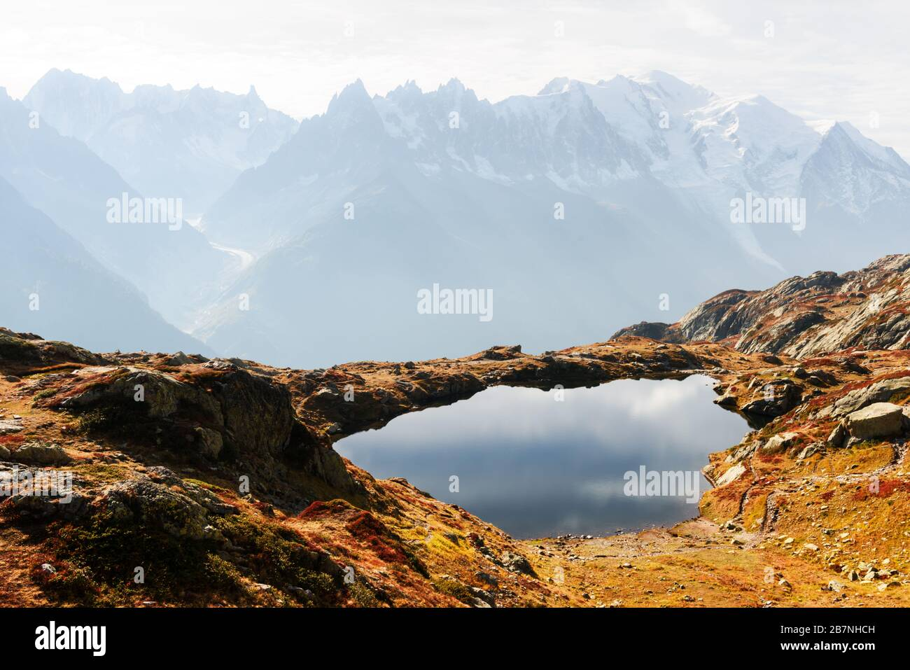 Colourful autumn landscape with Chesery lake (Lac De Cheserys) and snowy Monte Bianco mountains range on background. Vallon de Berard Nature Preserve, Chamonix, France Alps Stock Photo