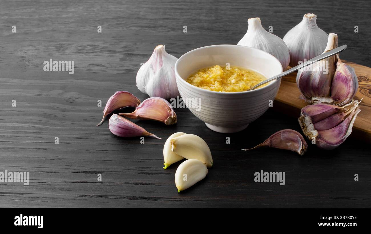 Garlic Cloves Bulb And Minced Garlic In Bowl On Dark Wood Background Stock Photo Alamy