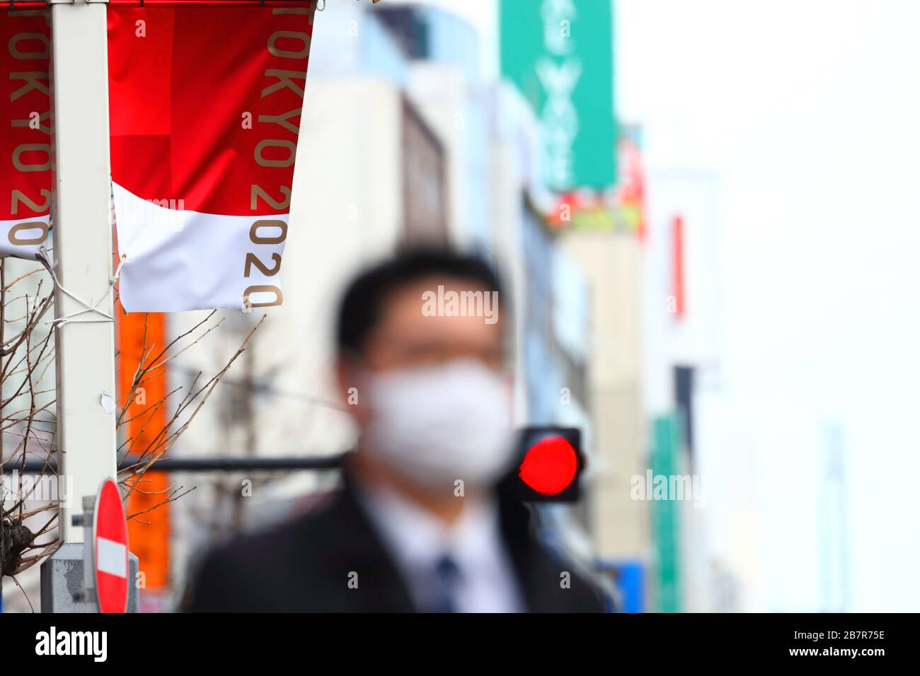 A man wearing a protective face mask walks in front of an Olympic Banner of Tokyo 2020 in Shinjuku, Tokyo, Japan on March 17, 2020. Credit: Naoki Nishimura/AFLO SPORT/Alamy Live News Stock Photo