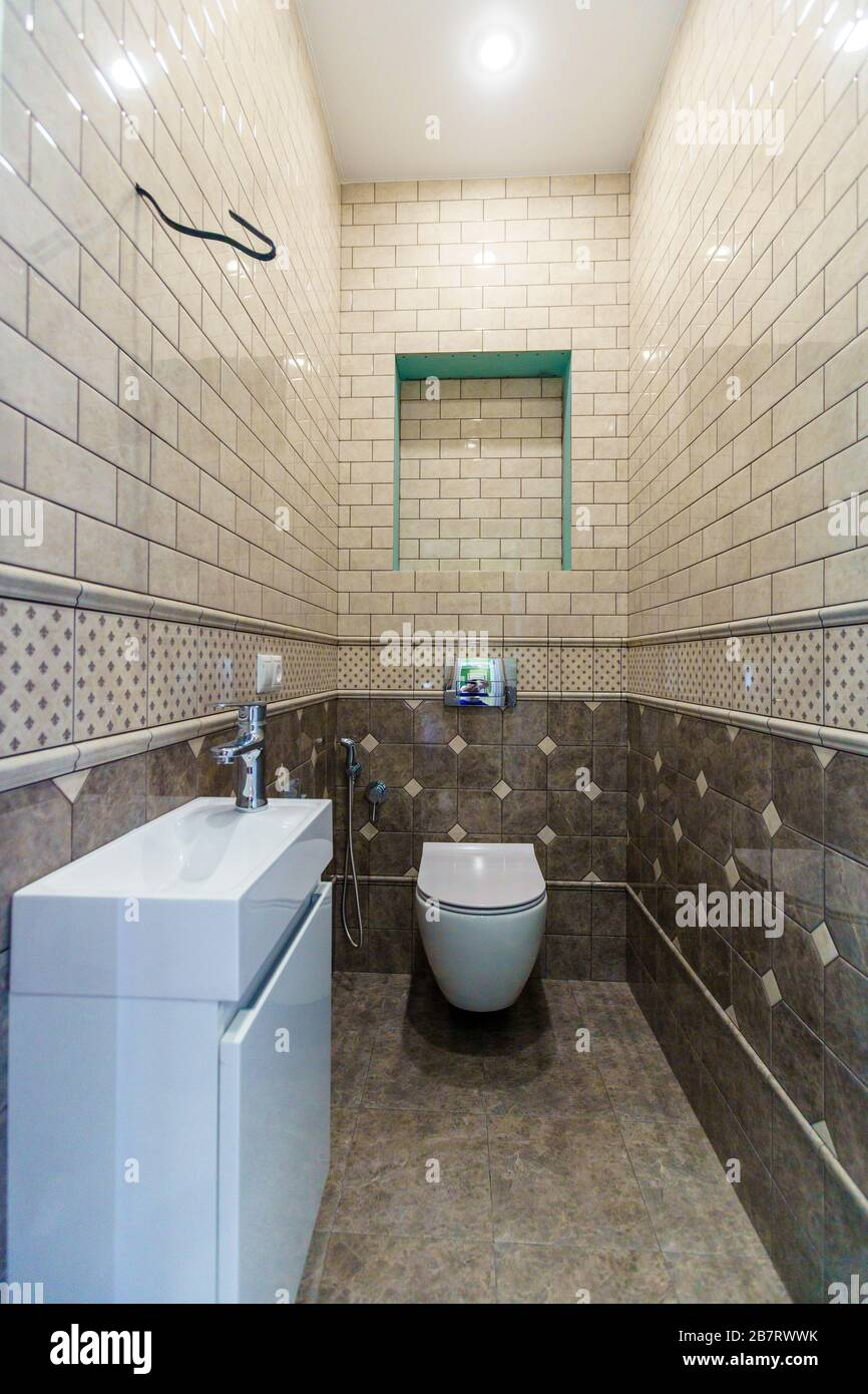 A Narrow Toilet With A Toilet Bowl And A Small Sink Beige Tiles On The Walls And Dark Beige Closer To The Floor Stock Photo Alamy