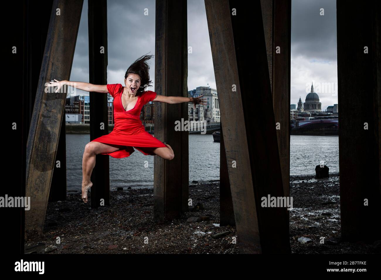 Female Dancer Leaping Mid Air under Pier, London, South Bank Stock Photo