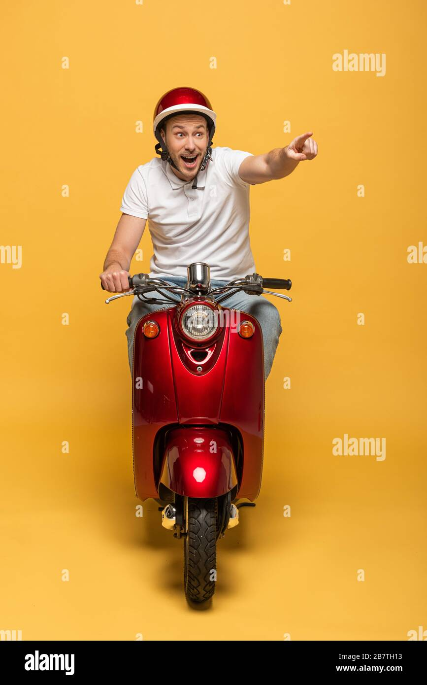 Happy Delivery Man In Helmet Riding Scooter And Pointing With Finger On Yellow Background Stock Photo Alamy