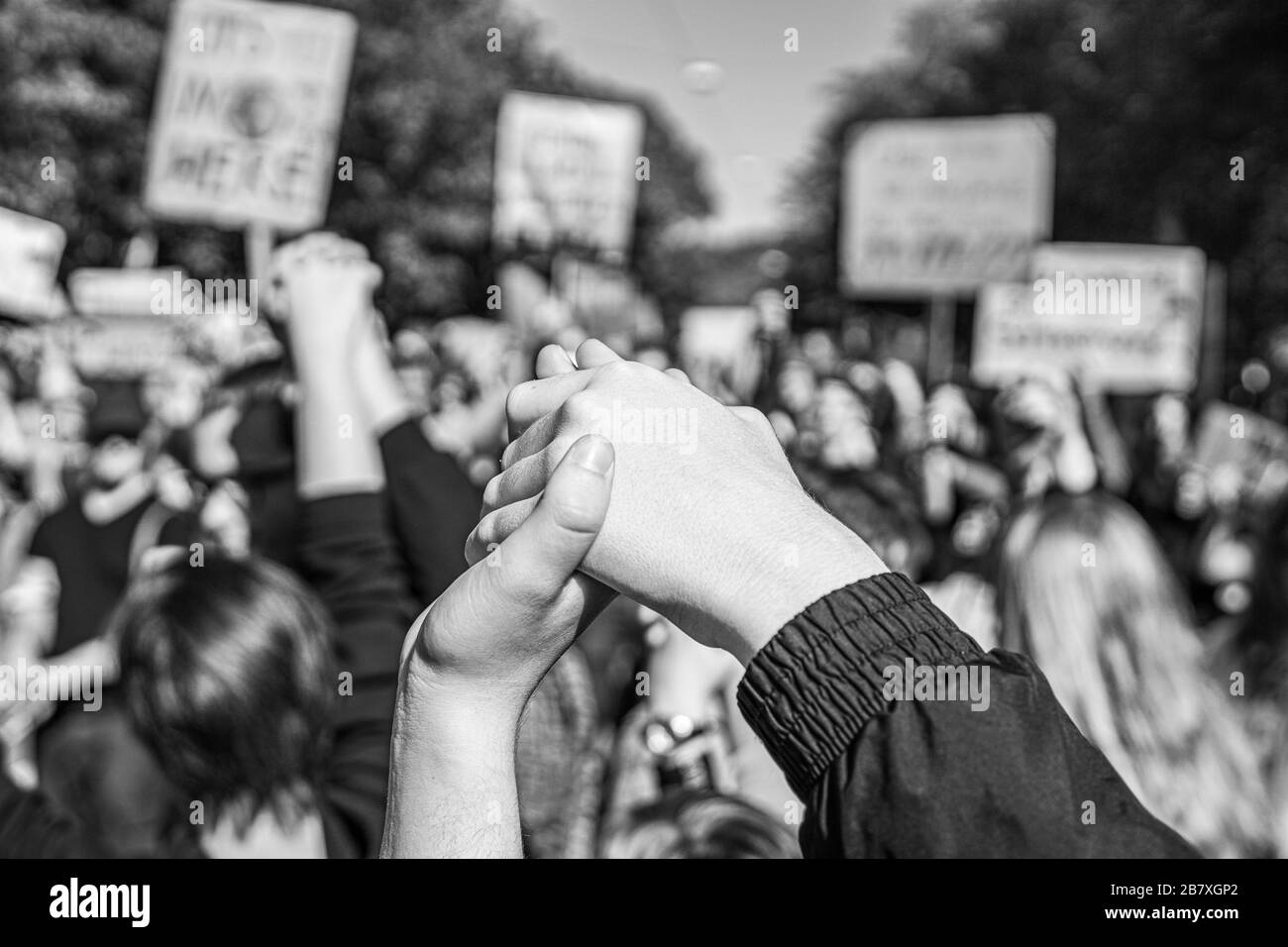 photograph in black and white of two people joining hands together at a fridays for future protest regarding climate change, symbolizing strength Stock Photo