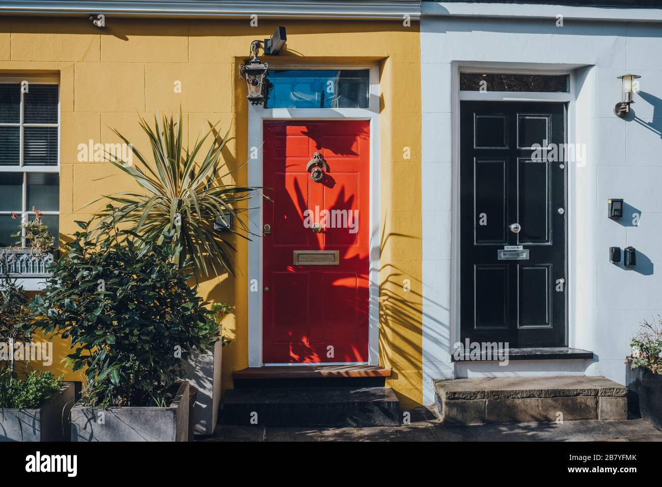 Colourful bright red front door on a yellow house in London, UK. Stock Photo