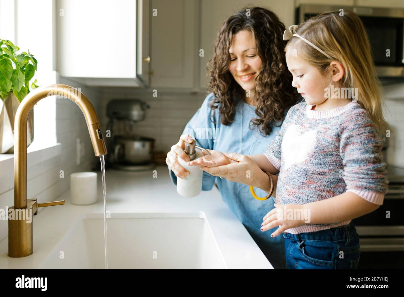 Mother and daughter washing hands in kitchen sink Stock Photo