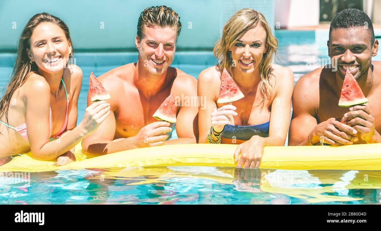 Happy friends eating watermelon in swimming pool villa resort - Cheerful people having fun in summer party - Main focus on right guys - Travel, holida Stock Photo