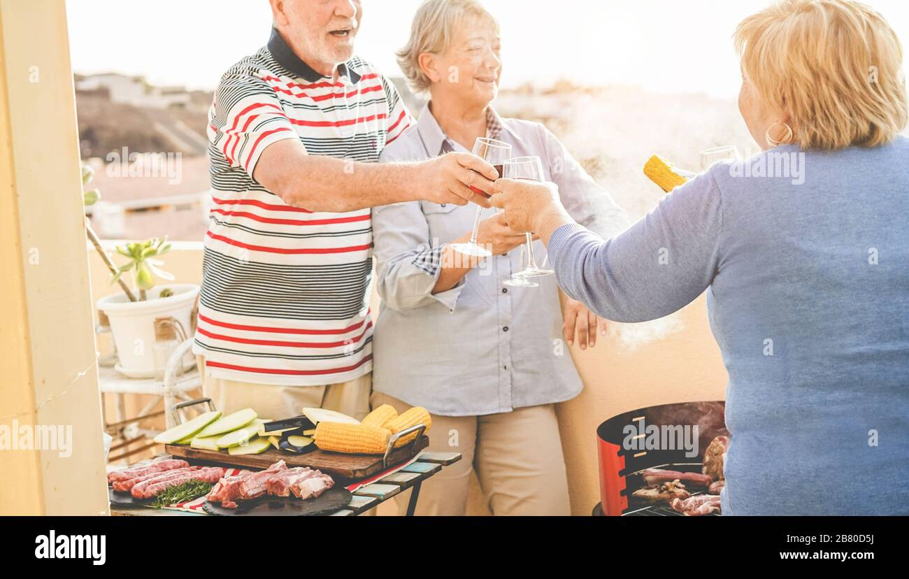 Group Of Happy Senior Friends Cheering At Barbecue Meal In Patio