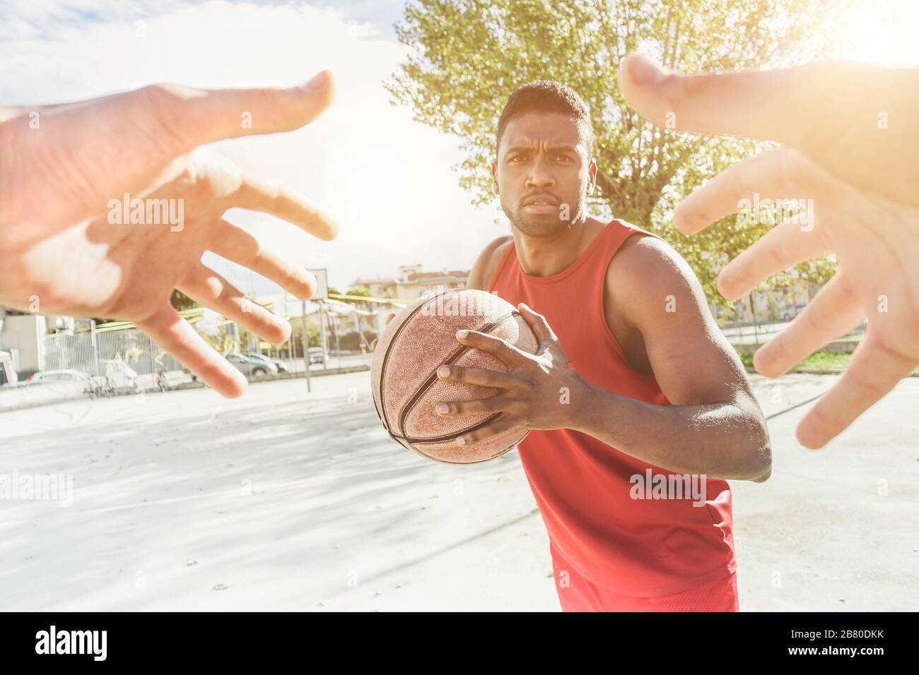 Multiracial basket player playing a game in urban quarter street camp outdoor with back lighting- Athlete hands trying to catch the ball from his oppo Stock Photo