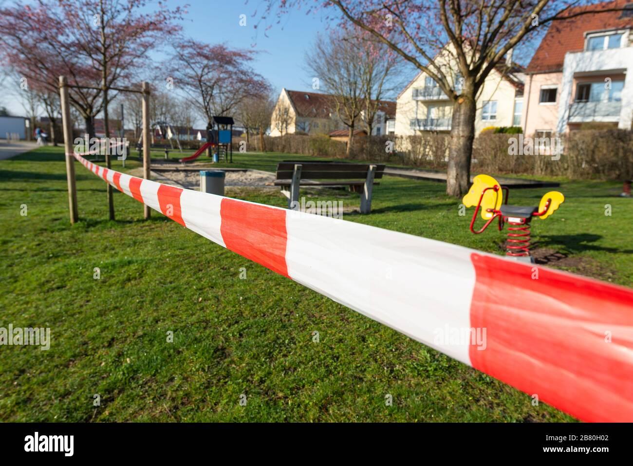 Rot-weisses Absperrband an einem gesperrten Kinderspielplatz während der Corona-Krise in Deutschland Stock Photo