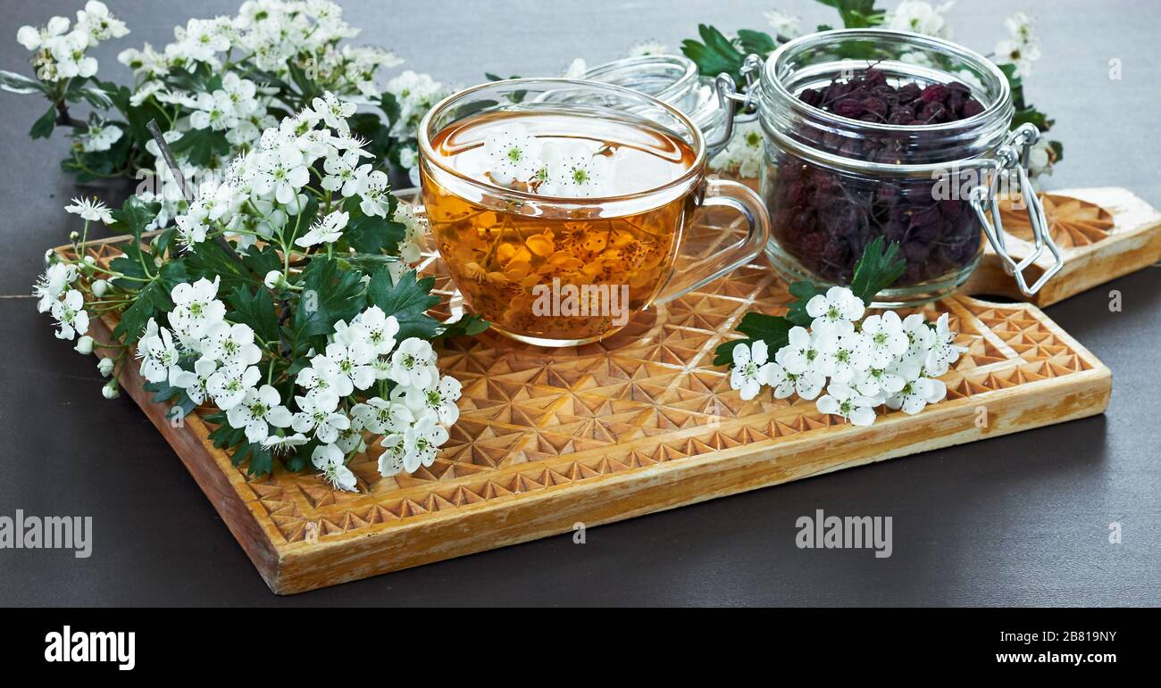 Herbal haw thorn tea from flower buds around blooming branches and a jar with berries on wooden cutting board, closeup, copy space, heart health and h Stock Photo