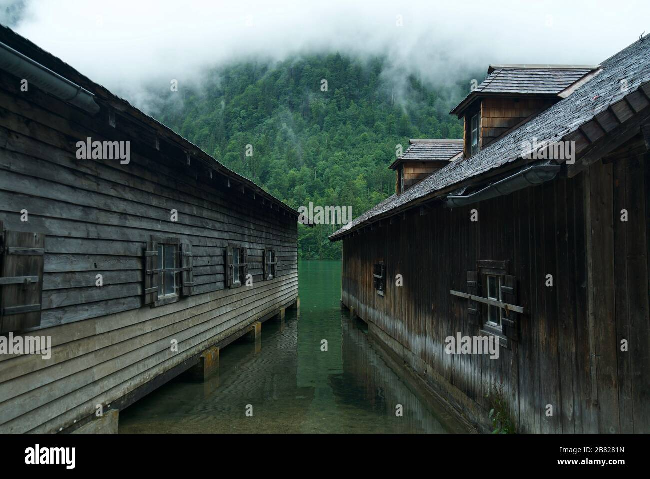 Boathouse / Boathouses by the water surrounded by mountains and clouds at Lake Königssee (Berchtesgaden National Park). Wooden cabins by the lake. Stock Photo