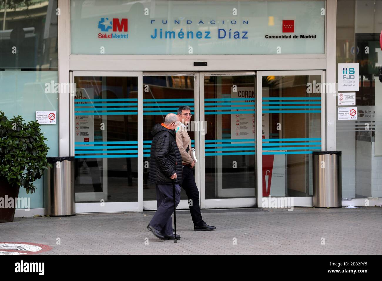 Madrid, Spain. 19th Mar, 2020. People walk outside the Jimenez Diaz Hospital in Madrid, Spain, 19 March 2020, where allegedly former Madrid Regional President Esperanza Aguirre and husband Fernando Ramirez have checked in for coronavirus. Credit: JUANJO MARTIN/EFE/Alamy Live News Stock Photo