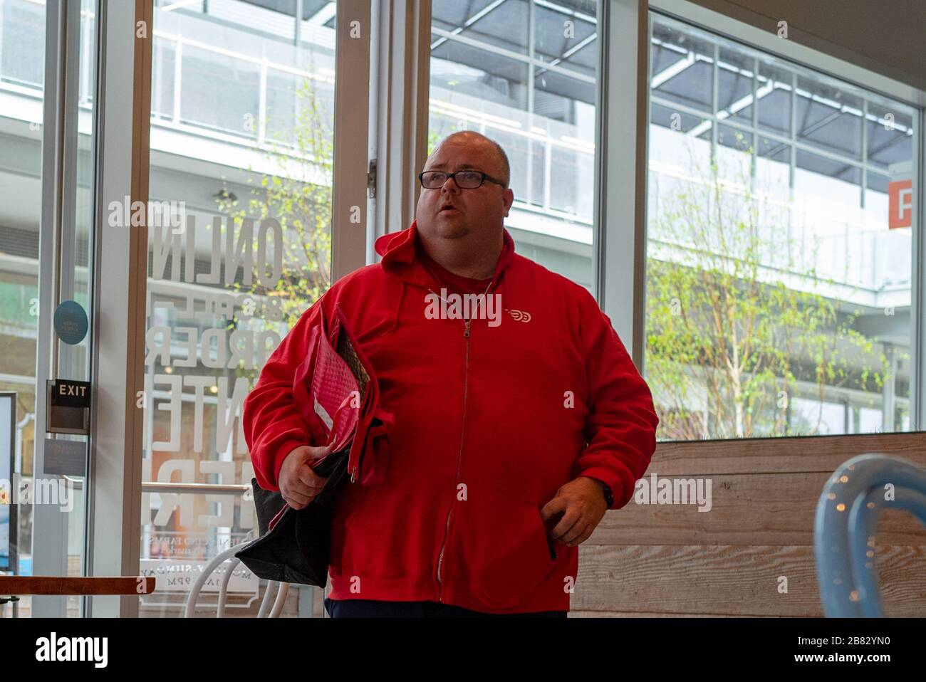 A Doordash driver wearing a red branded hoodie and carrying a food bag picks up an order at a restaurant in Contra Costa County, San Ramon, California during an outbreak of the COVID-19 coronavirus, March 14, 2020. Amid the outbreak, many residents have turned to food delivery services as a way to obtain meals, as restaurants have been ordered to close their dining rooms. () Stock Photo