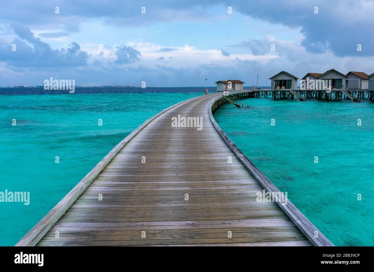North Malé Atoll, Maldives - December 29 2019 - A wooden pier towards the water villas Stock Photo