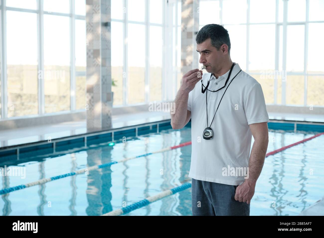 Experienced gray-haired male coach with stopwatch hanging on neck blowing whistle to swimmer in indoor pool Stock Photo
