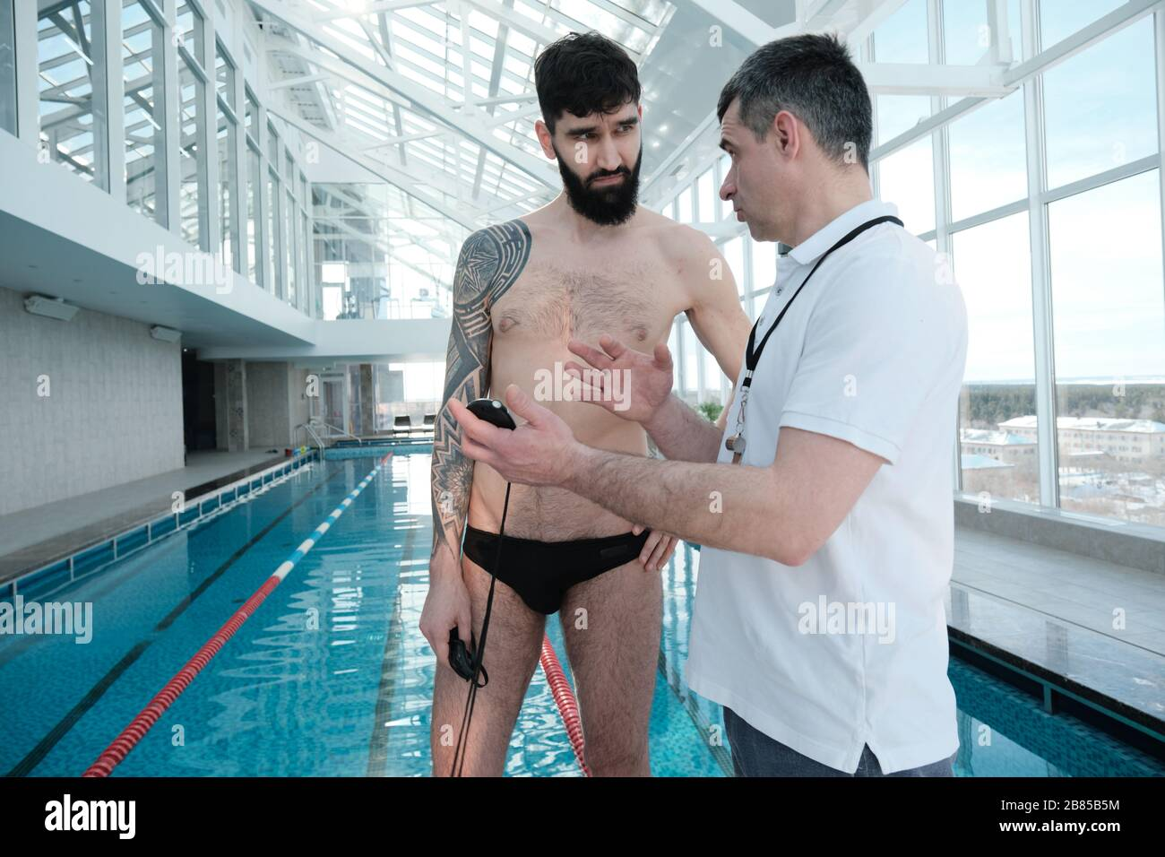 Experienced mature coach showing stopwatch and explaining mistakes to swimmer in indoor pool Stock Photo