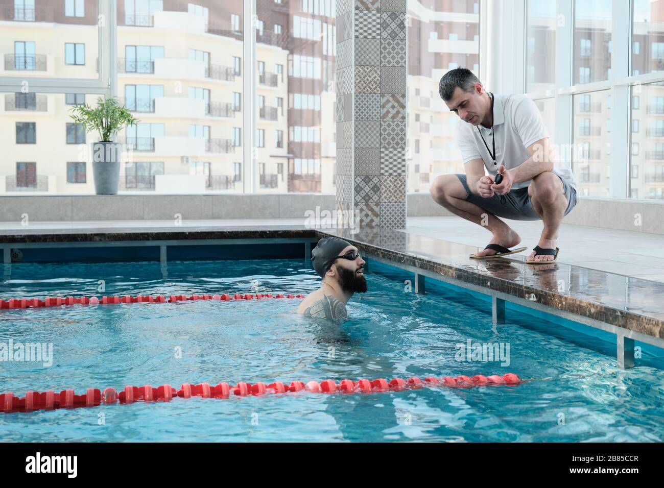 Experienced coach crouching on edge of poolside and showing time on stopwatch to swimmer while discussing his results Stock Photo