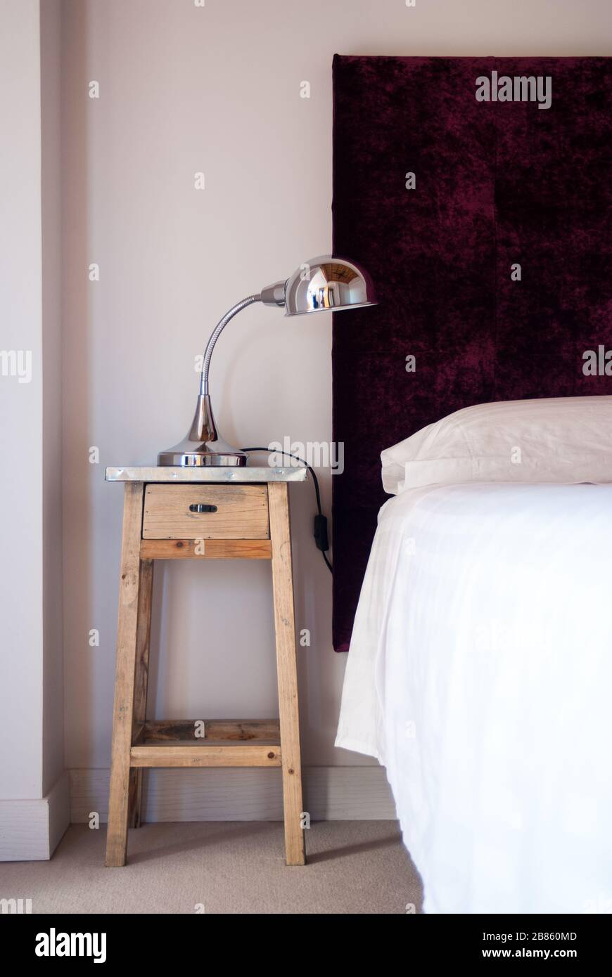 Wooden Bedside Table Next To A Comfortable White Bed Stock Photo Alamy