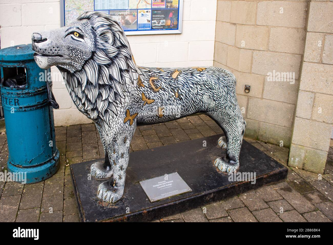 "A lion sculpture known locally as ""Lionardo"" painted  by a local artist is decorated with gold insects on a white and black background in the town of Stock Photo"