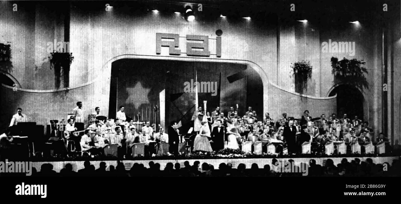 """""""Italiano: Festival di Sanremo 1957. Al centro del palcoscenico, vi sono i presentatori Marisa Allasio, Nunzio Filogamo e Fiorella Mari. Partecipano l'orchestra Angelini a sinistra e l'orchestra Trovajoli a destra. English: The 1957 San Remo Music Festival. At the centre of the stage are the presenters Marisa Allasio, Nunzio Filogamo and Fiorella Mari. The Angelini orchestra (on the left) and the Trovajoli orchestra (on the right) took part in the event.; 1957; Radiocorriere; The photographer is unknown; """" Stock Photo"""