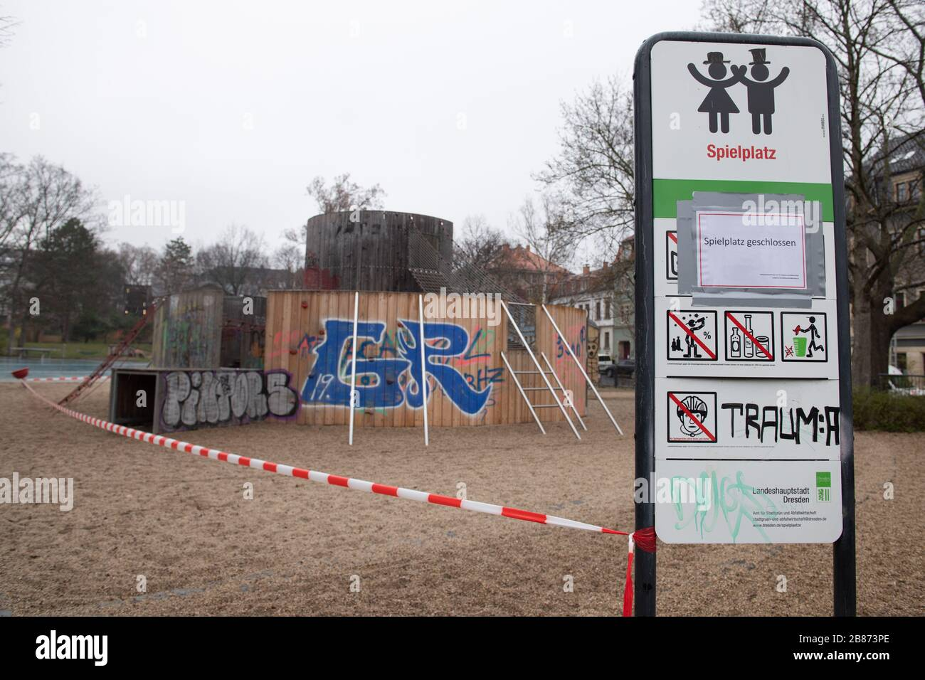 """Dresden, Germany. 20th Mar, 2020. A sign with the inscription """"Spielplatz geschlossen"""" (Playground closed) is stuck to a sign on a playground next to a barrier tape. To slow down the spread of the corona virus, the federal government has severely restricted public life. Credit: Sebastian Kahnert/dpa-Zentralbild/dpa/Alamy Live News Stock Photo"""