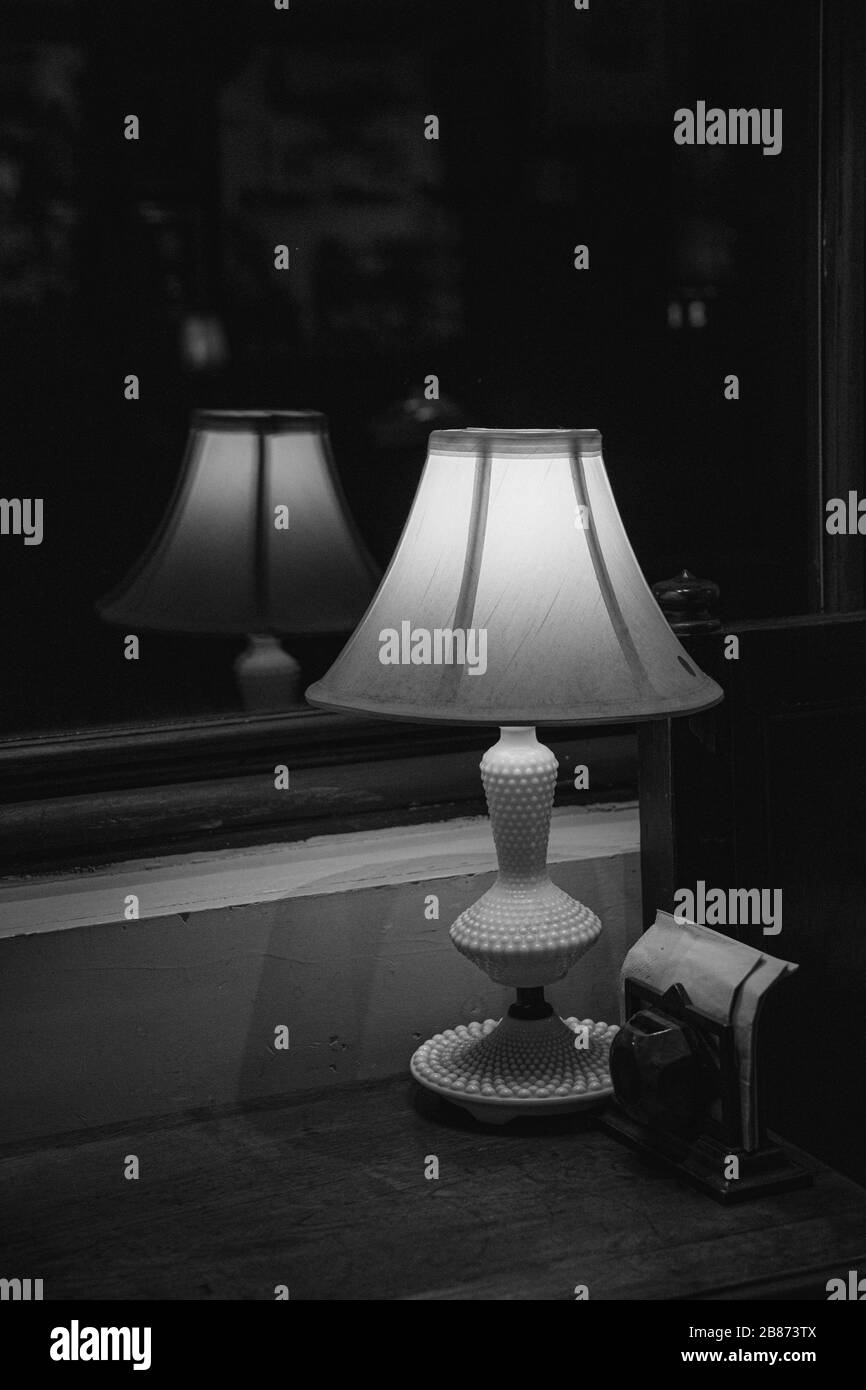 Black And White Still Life Of Elegant Shiny Antique Table Lamp Closeup On Dark Blurry Background Lamp Silhouette Blurred Reflection In Glass Window Stock Photo Alamy