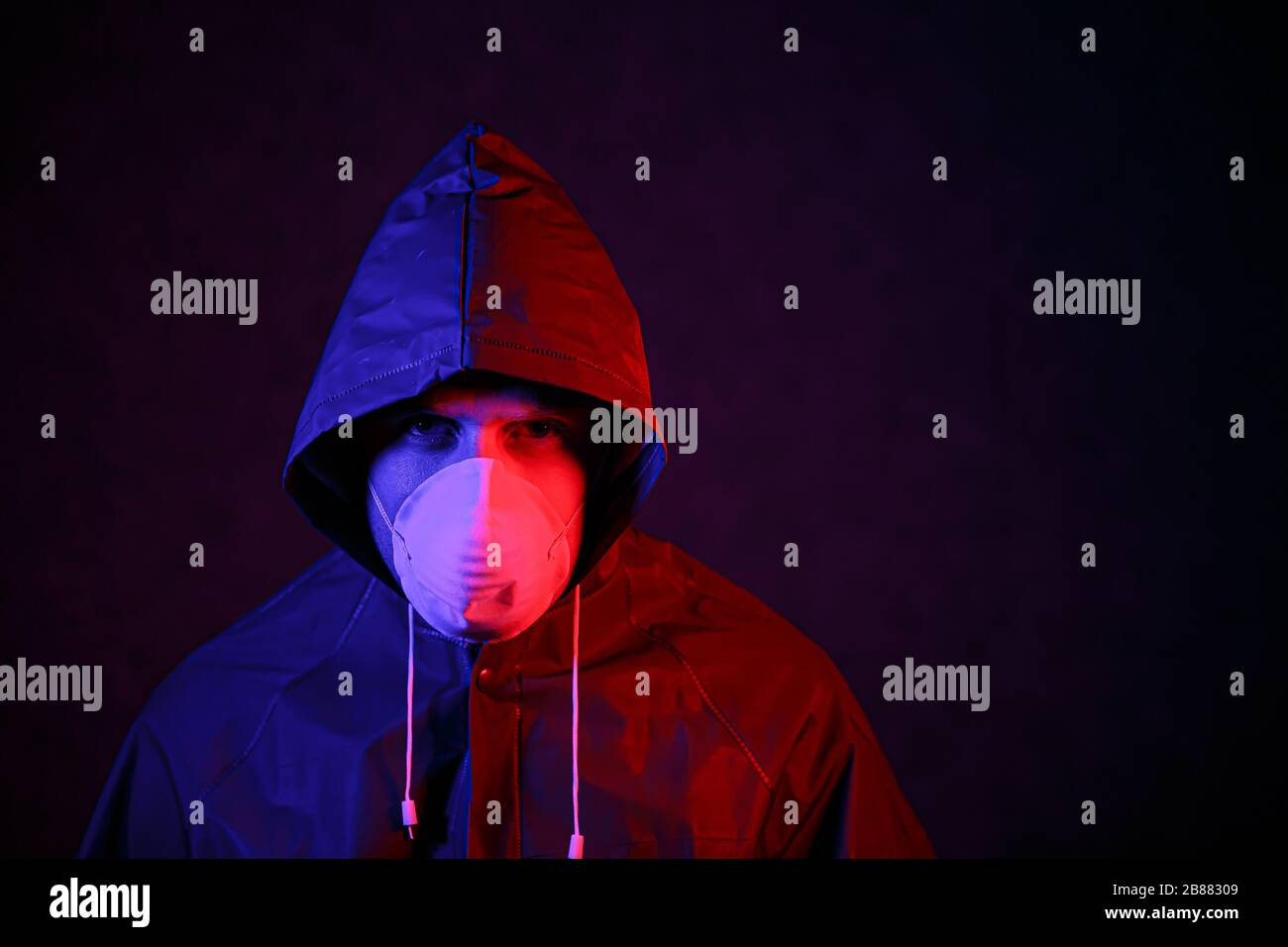 Coronavirus. A man in a mask and chemical protection suit in red and blue light. Fight against the virus Stock Photo