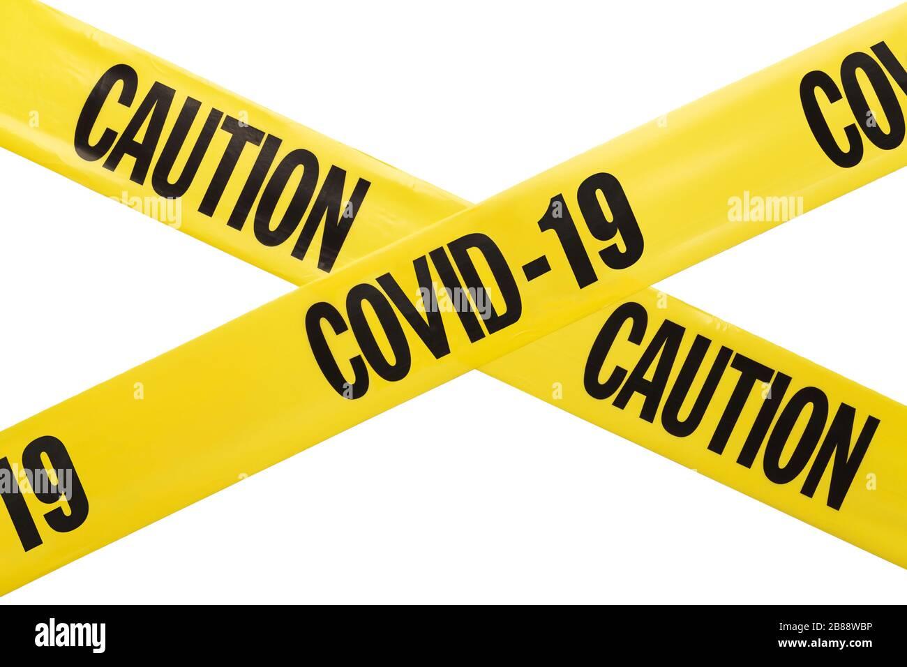 Yellow Plastic Coronavirus Caution Tape Criss Crossing Isolated on White Background. Stock Photo