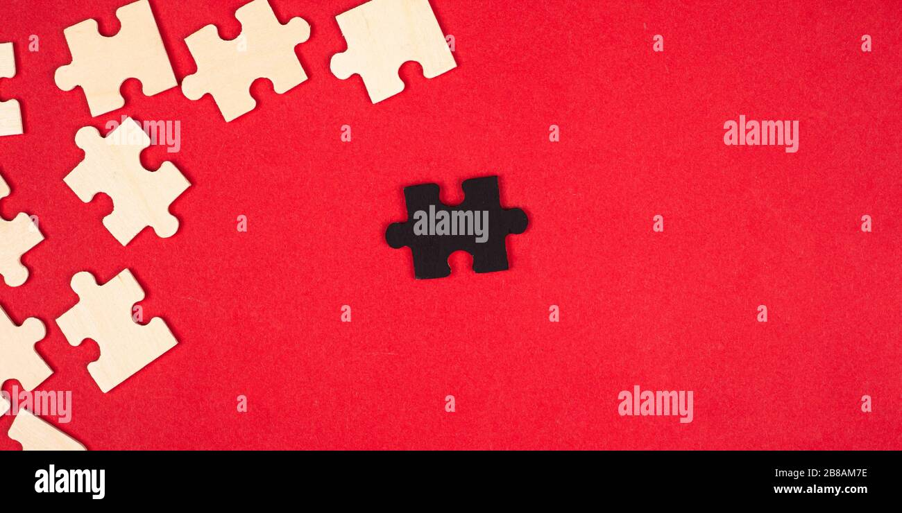 wooden white and black puzzles on a red background close-up top view. outcast antisocial leader differ from others children's educational toy. Stock Photo