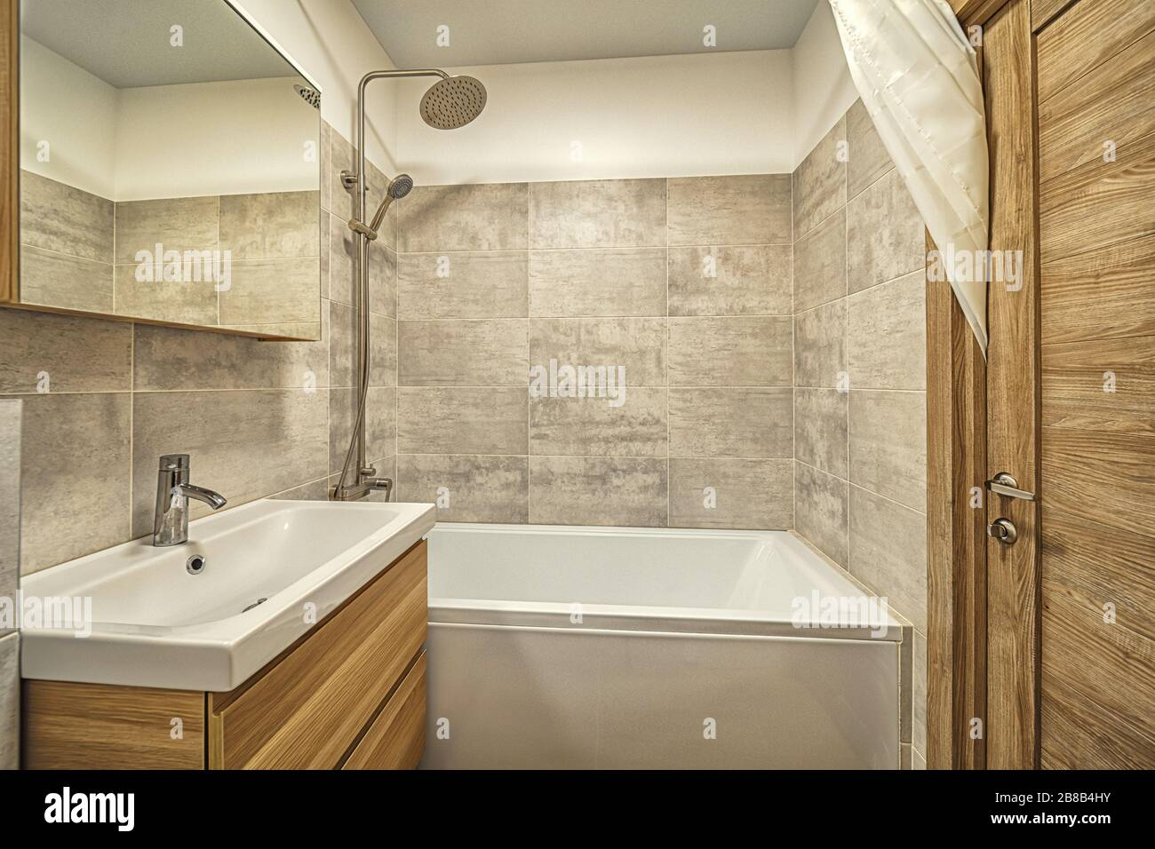 Bright clean Small beige tile bathroom with bath tube and sink