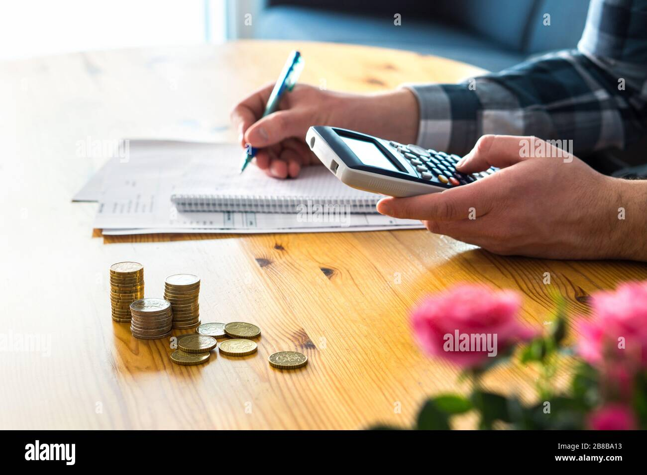 Man using calculator and counting budget, expenses and savings. Low income family living cost and rising prices concept. Calculating and budgeting. Stock Photo