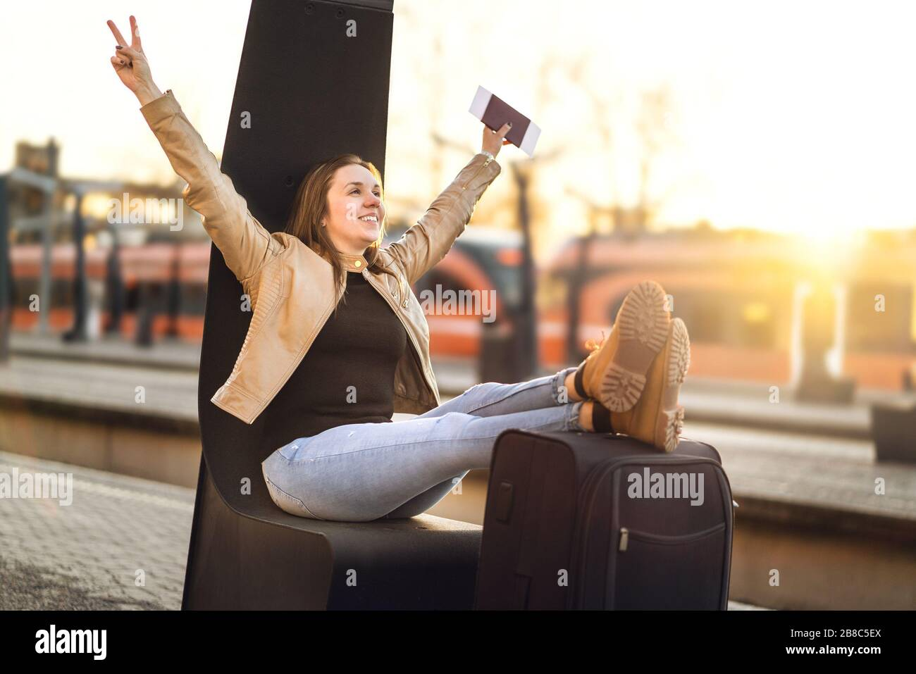 Finally on vacation. Woman celebrating at train station to leave on fun trip. Happy smiling person with legs and shoes on suitcase and luggage. Stock Photo