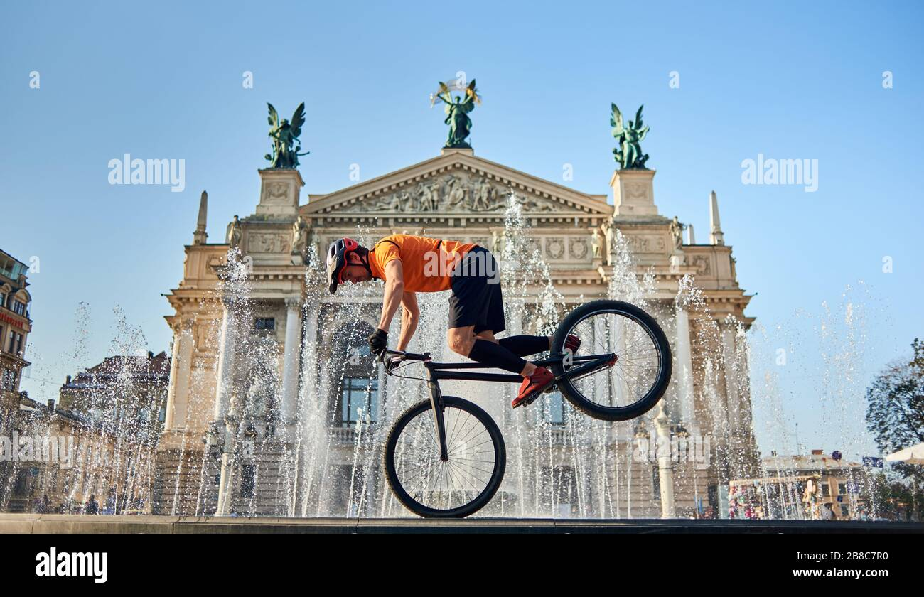Front view of cyclist standing on front wheel of mountain bike and looking down. Young athlete is cycling downtown near fountain. Concept of active. Stock Photo