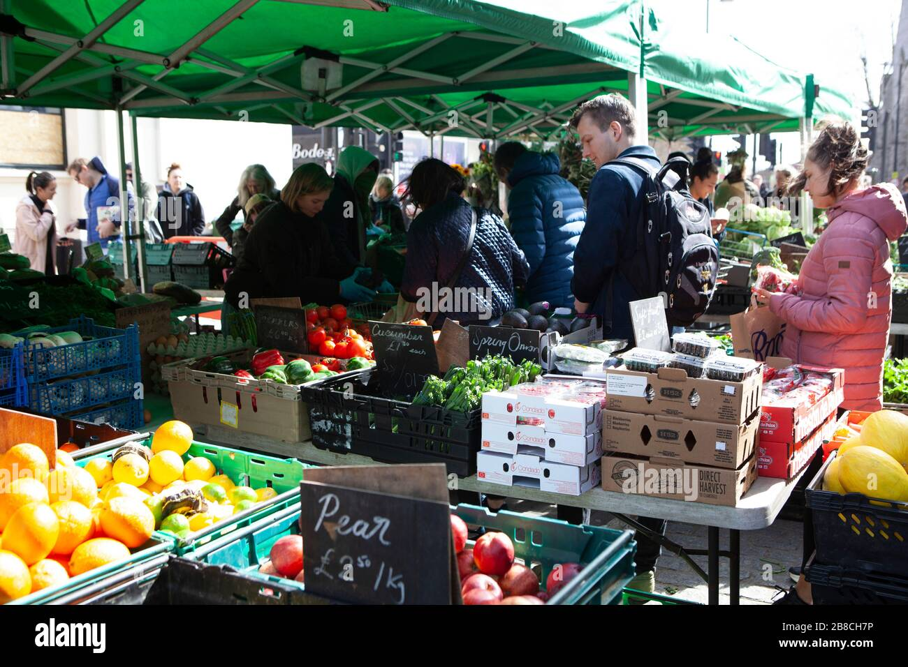 London, UK. 21st March 2020.  at Venn Street in Clapham shoppers appreciate fresh fruit and vegetables available at the weekly Saturday market. However, very few wore face masks or observed social distancing advice. Credit: Anna Watson/Alamy Live News Stock Photo