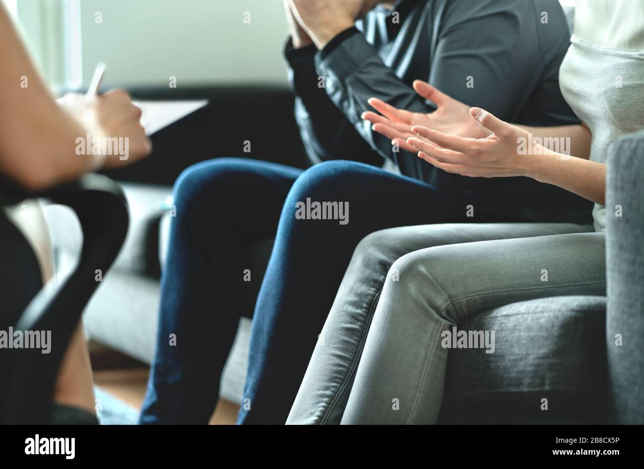 Angry couple argue in therapy. Dispute in marriage counseling. Custody battle, divorce, adoption, alimony, prenup or family problem. Stock Photo